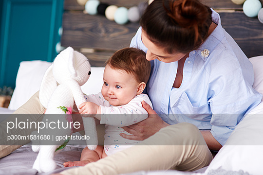 Mother and baby playing on bed at home - p300m1581680 von gpointstudio