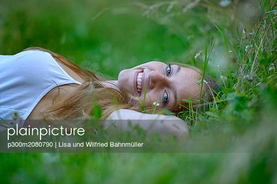 Portrait of happy teenage girl relaxing on a meadow in summer - p300m2080790 by Lisa und Wilfried Bahnmüller