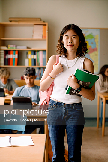 Portrait of teenage girl with book and backpack in classroom - p426m2298649 by Maskot