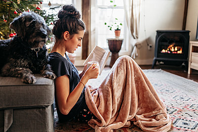 young woman reading by the fireplace with dog, drinking a hot beverage - p1166m2235089 by Cavan Images