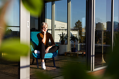 Woman sitting in armchair looking out of window - p300m2081138 by Rainer Berg