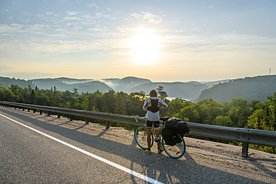 Cyclist stopping on road with scenic view, Ontario, Canada - p924m2237502 by Alex Eggermont