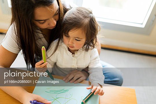 Nanny helping a toddler with a drawing with colored pencils - p1166m2085001 by Cavan Images