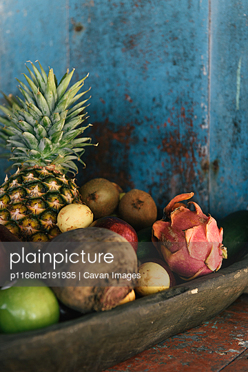 Wooden bowl of fresh tropical fruits at an outdoor bar in Mexico - p1166m2191935 by Cavan Images