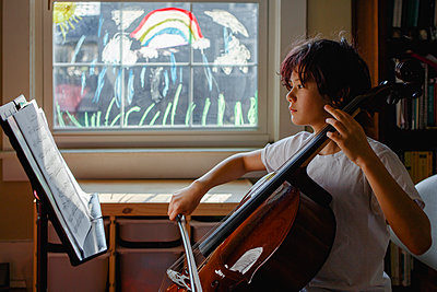 A focused boy sits in front of painted window practicing cello - p1166m2190537 by Cavan Images