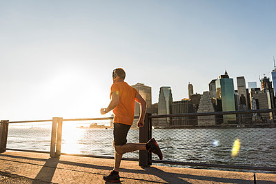 USA, Brooklyn, man jogging in front of Manhattan skyline in the evening - p300m1205631 by Uwe Umstätter