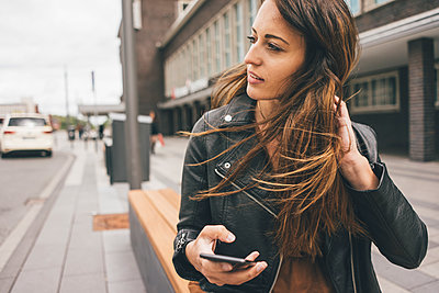 Young woman with windswept hair holding cell phone in the city - p300m2004660 von Kniel Synnatzschke
