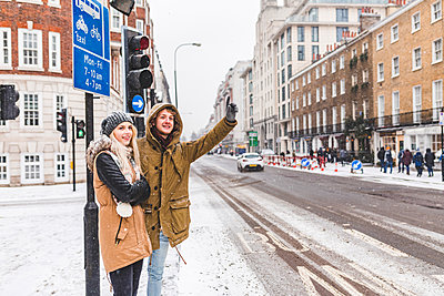 UK, London, young couple standing at roadside hailing taxi in winter - p300m2013237 by William Perugini
