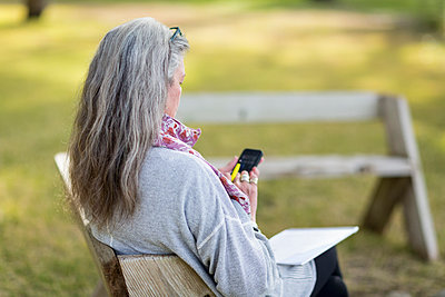 Older Caucasian woman using cell phone outdoors - p555m1413784 by Marc Romanelli