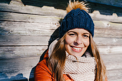 Young woman in winter clothing at log cabin - p586m2005083 by Kniel Synnatzschke