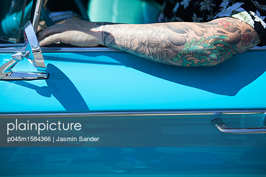 Tätowierter Mann sitzt im Buick Oldtimer - p045m1584366 von Jasmin Sander