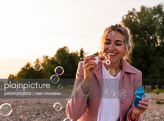 Laughing blond woman and soap bubbles - p300m2005333 von Uwe Umstätter