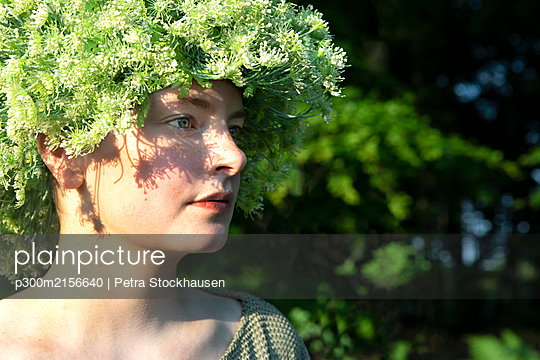 Portrait of young woman wearing headpiece of flowers - p300m2156640 by Petra Stockhausen