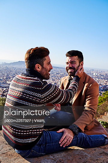Romantic male couple sitting on observation point against clear sky, Bunkers del Carmel, Barcelona, Spain - p300m2257327 by Veam