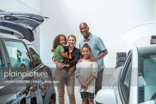 UK, Portrait of smiling family with daughter (2-3) and son (8-9) in car showroom - p924m2300786 by Monty Rakusen