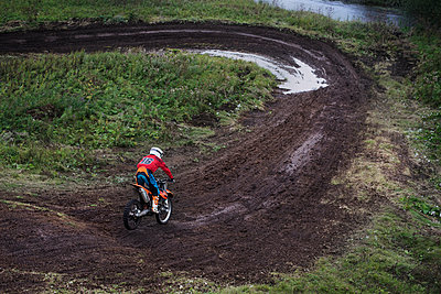 Rear view of man riding dirt bike on field - p1166m1099684f by Cavan Images
