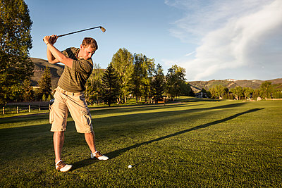 Golfer swinging golf club while standing on grassy field - p1166m969364f by Cavan Images