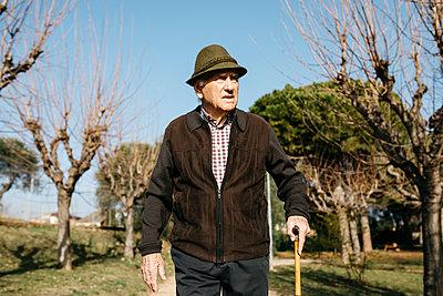 Spain, Barcelona. Retired senior man walking through a park in winter with his cane - p300m2166545 von Josep Rovirosa