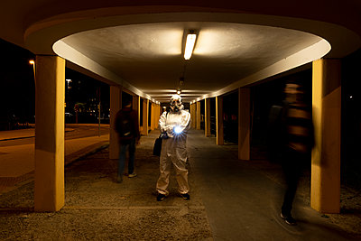 Senior woman wearing protective suit and mask in the city at night - p300m2170124 by Eloisa Ramos