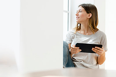 Young brunette woman at home sitting on window bench and looking outside while holding her tablet - p300m2181113 by Steve Brookland