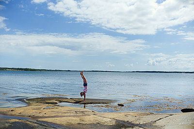 Girl doing handstand at water - p312m800478f by Johan Willner