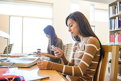 Student using cell phone at desk in library - p555m1453295 by John Fedele