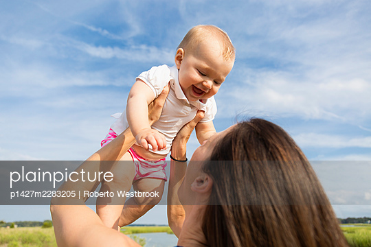 Mid adult woman holding up baby daughter on riverside - p1427m2283205 by Roberto Westbrook