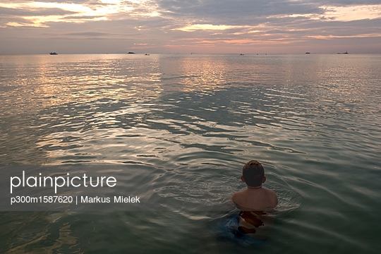 Thailand, boy swimming in the at sunset - p300m1587620 von Markus Mielek