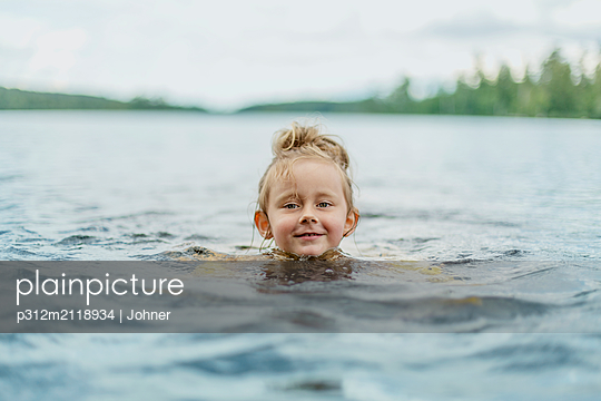 Girl swimming in lake - p312m2118934 by Johner
