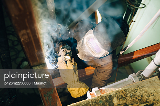 Young worker using welding torch while working at site - p426m2296033 by Maskot