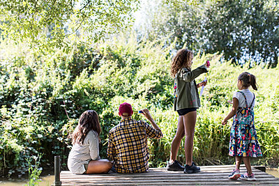 Family blowing bubbles on remote dock in woods - p1023m2066740 by Sam Edwards