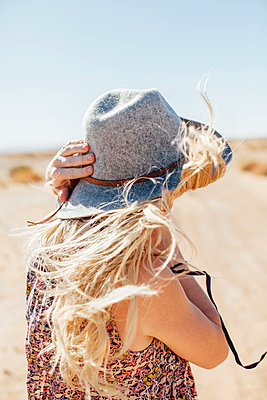 Woman in sun hat standing against at desert against clear sky during sunny day - p1166m1227798 by Cavan Images