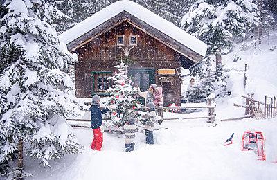 Austria, Altenmarkt-Zauchensee, family decorating Christmas tree at wooden house - p300m2069912 by Hans Huber