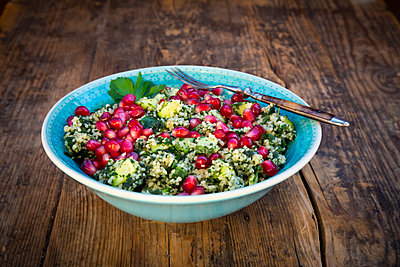 Bowl of bulgur wheat salad with cucumber, herbs, pomegranate seed and parsley - p300m2083728 by Larissa Veronesi