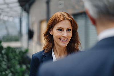 Portrait of smiling businesswoman talking to businessman in office - p300m2156339 by Joseffson