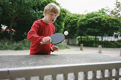Disabled boy playing table tennis in park - p301m1180569 by Halfdark