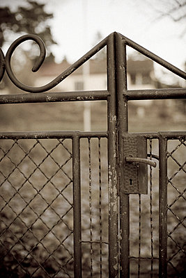 An iron gate in front of an old house Gotland Sweden - p31222324f by Johan Odmann