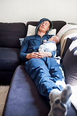 Father sleeping on sofa with baby son - p312m1131462f by Rebecca Wallin