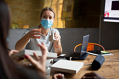 Female colleagues discussing over product in office during pandemic - p426m2270396 by Maskot