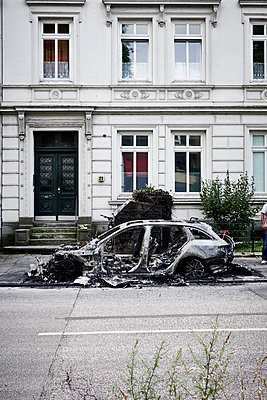Burned car in front of a building - p851m1481658 by Lohfink