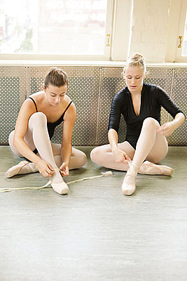 Ballerinas putting on ballet slippers - p9245551f by Image Source