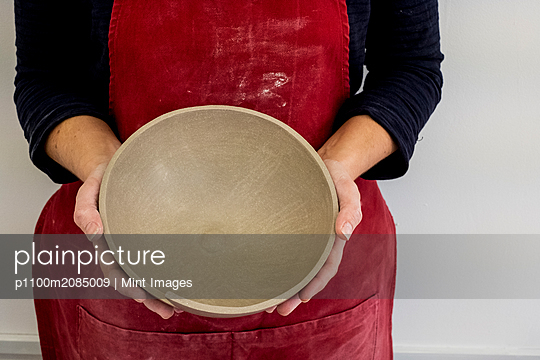Close up of ceramic artist wearing red apron working on clay bowl. - p1100m2085009 by Mint Images