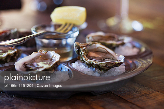 Oyster shells served on table - p1166m1151204 by Cavan Images