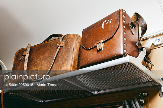 Old suitcases on the luggage rack in a train compartment - p1540m2259018 by Marie Tercafs