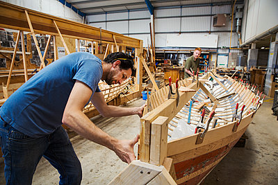 Two men in a boat-builder's workshop, working together on a wooden boat hull. - p1100m1490077 by Mint Images