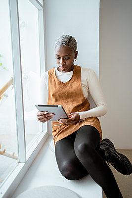 Serious woman looking at digital tablet while sitting by window in living room - p300m2277405 by Rafa Cortés