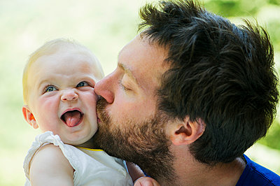 Father kissing baby's cheek - p624m1180487 by Frederic Cirou