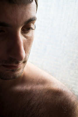 Sad young man looking away  - p794m1092333 by Mohamad Itani