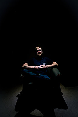 Man in the dark sitting on armchair - p795m2044777 by Janklein