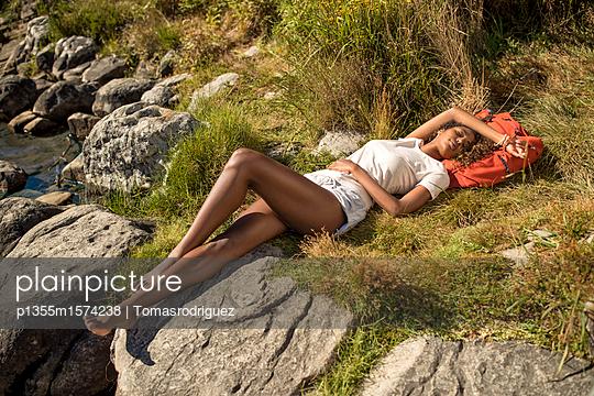 Junge Frau macht eine Pause beim Wandern - p1355m1574238 von Tomasrodriguez